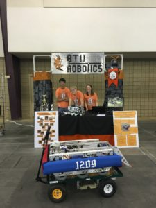 Shamik, Tucker, and Sarah in Team 1209's booth